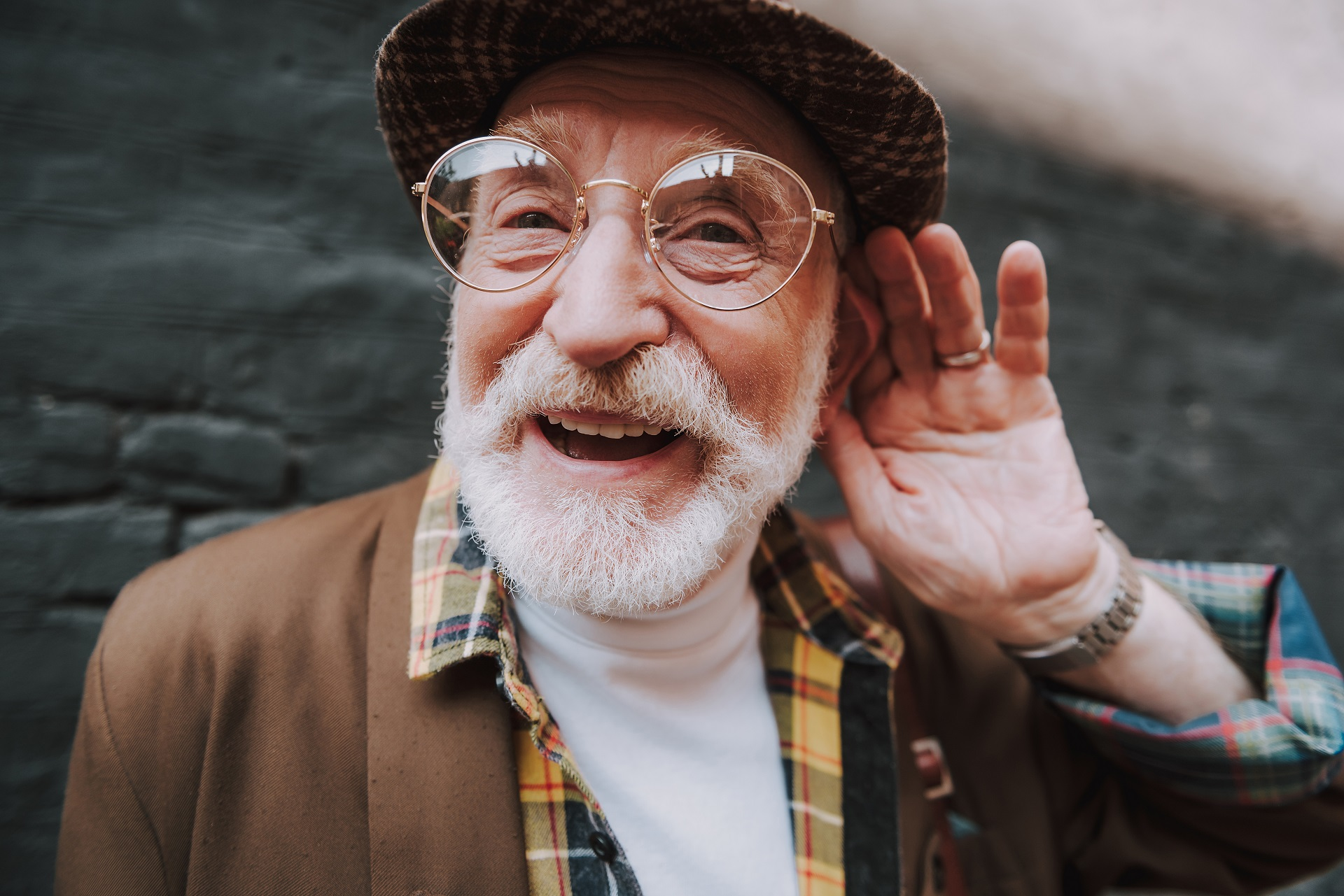 Portrait of old stylish hearing impaired man